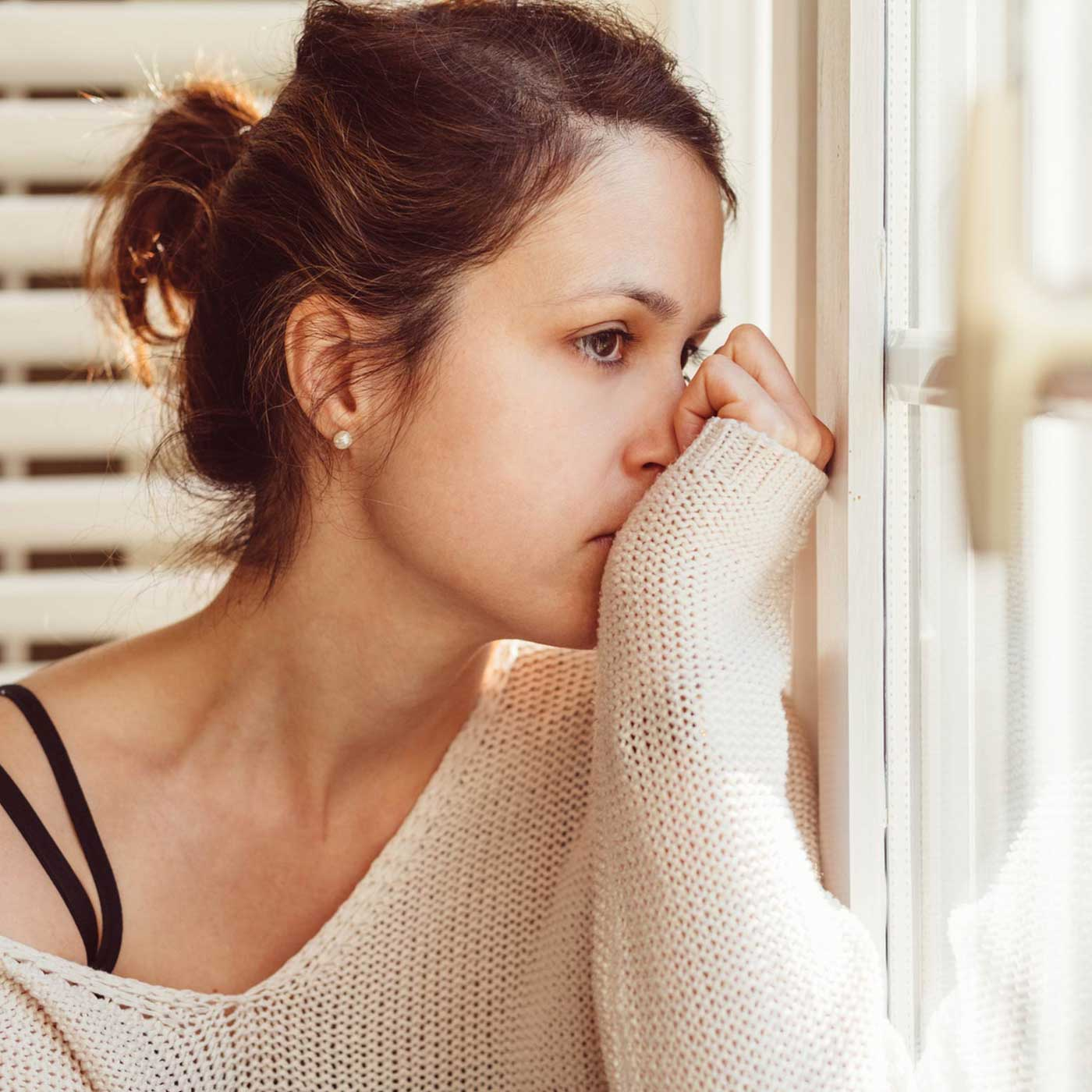 Essential Chiropractic and Healthcare Clinic - Help and Treatments for Nervous System Conditions Woman by the Window